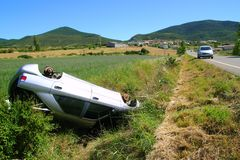 Car crash accident upside down vehicle. Off the road green landscape Stock Photography