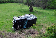Car crash accident. Upside down vehicle off the green landscape Royalty Free Stock Photo