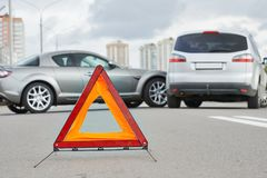 Accident or crash with two automobile. Road warning triangle sign in focus Stock Images
