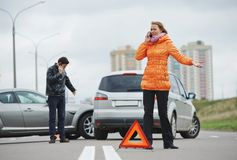 Car crash collision. Car collision. driver men and women examining damaged automobile cars after crash accident in city royalty free stock image