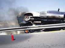 Car crash on highway. A car crash on a highway in Mexico. Wheels burning, fire extinguisher stock photos