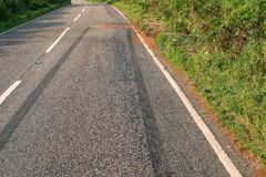 Car crash scene. Skid marks left in the road after a car crash on a rural road stock photos