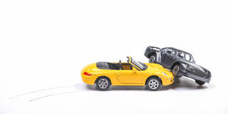 Car crash between sportscar and sedan. Car crash between a yellow sportscar and a black sedan with brake tracks. Simulation with model cars Royalty Free Stock Photo