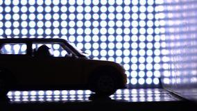 Car with crash-test dummy hitting the wall. Crash test laboratory concept. Purple lights background, super slow motion
