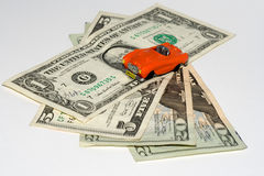 Car on credit. Small red car on the US dollars Royalty Free Stock Images