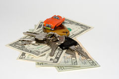 Car on credit. Small red car on the US dollars and keys Royalty Free Stock Image