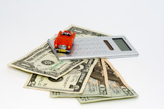 Car on credit. Small red car on the US dollars and calculator Royalty Free Stock Photo