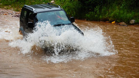 Car crossing through water. A car passing through muddy water with big splash in front on the hood Stock Image