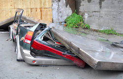 Car Crushed in Earthquake. A car is crushed by a collapsed concrete wall following a 6.2 magnitude earthquake Stock Image