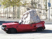 Car crushed by rock. Red car smashed by a huge rock - on display in a roundabout in Syndey, Australia Stock Photos