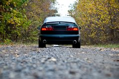 Car on curvy autumn forest road Stock Images