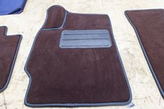 Car 3D handmade floor mats of brown color from wool for front and rear passengers of a vehicle in an interior design workshop with. Tools royalty free stock images
