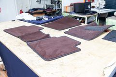 Car 3D handmade floor mats of brown color from wool for front and rear passengers of a vehicle in an interior design workshop with. Tools stock photo