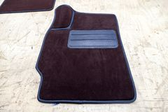 Car 3D handmade floor mats of brown color from wool for front and rear passengers of a vehicle in an interior design workshop with. Tools royalty free stock photo