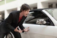 Car damage. Man expressing anger because someone broke his car mirror Royalty Free Stock Photography