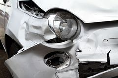 Car Damage. Damage to the front of a white car after an accident Stock Photo