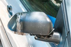 Car with damaged and broken side rear mirror glued with duct tape close up selective focus.  stock image