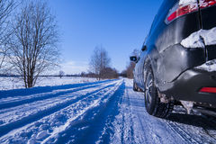 Car on a dangerous road covered with snow and ice. Snow-covered road in winter, no asphalt, car on a dangerous stretch of road covered with snow and ice Royalty Free Stock Photography