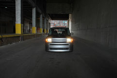Car in a dark warehouse. A silver compact car in a dark warehouse loading tunnel. See my portfolio for more automotive images stock image