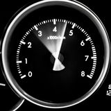 Car dashboard dials - engine RPM rotations per minute. On black background stock photography