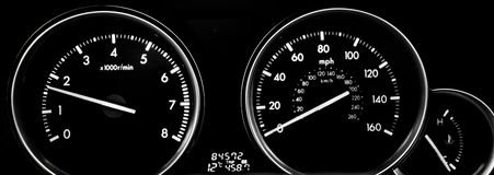 Car dashboard dials - engine RPM and speedometer. Isolated on black background royalty free stock photos