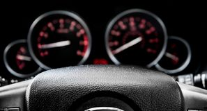 Car dashboard dials - engine RPM and speedometer. Isolated on black background stock photo