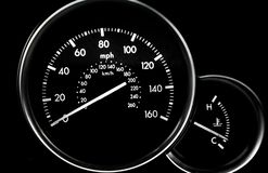 Car dashboard dials - speedometer and engine temperature gauge. On black background stock images