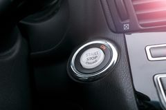 Car dashboard with focus on engine start stop button, Modern car interior details. Start/stop. Soft lightning. Car dashboard with focus on engine start stop Stock Photography