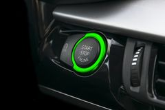Car dashboard with focus on green engine start stop button. Car interior details. Car detailing. Car dashboard with focus on green engine start stop button. Car royalty free stock images