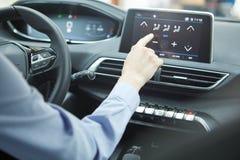 Car dashboard. Radio closeup. Woman sets up air conditioning. Car dashboard. Woman sets up air conditioning Royalty Free Stock Images