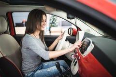 Car dashboard. Radio closeup. Woman sets up button on dashboard Royalty Free Stock Photography