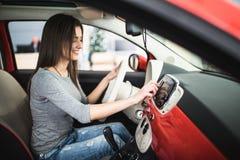 Car dashboard. Radio closeup. Woman sets up button on dashboard. Car dashboard. Radio closeup. Woman sets up radio royalty free stock photography