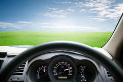 Car dashboard speeds while on green grass and sky. car driving f Stock Photo