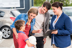 Car dealer advising family on buying auto Royalty Free Stock Image