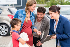 Car dealer advising family on buying auto Royalty Free Stock Photos
