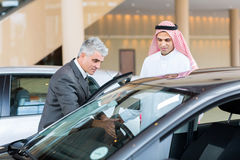 Car dealer Arabian buyer. Middle aged car dealer showing new car to potential Arabian buyer Royalty Free Stock Images