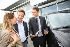 Car dealer with couple buying new car Royalty Free Stock Photo