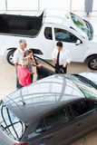 Car dealer customers. Overhead view of car dealer showing new car to customers Stock Photo