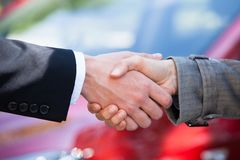 Car dealer and female client shaking hands at dealership Royalty Free Stock Photos