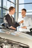 Car dealer giving client keys Stock Photo