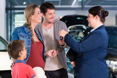 Car dealer giving key to new auto to family Royalty Free Stock Image