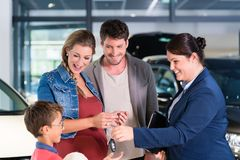 Car dealer giving key to new auto to family Stock Image