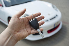 Car dealer. Car key in car dealer hands against blurred new white sport car in the background Stock Photography