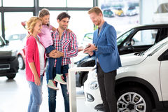 Car dealer offering a car to family Royalty Free Stock Images