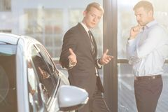 Car dealer offering expensive vehicle Stock Photo