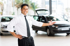 Car dealer presenting new vehicle. In showroom Stock Images