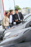 Car dealer showing brochure to clients. Car dealer showing vehicles to couple Royalty Free Stock Photography