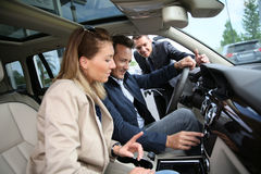 Car dealer showing a car on sale to potential buyers Stock Image
