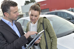 Car dealer showing specs on tablet Royalty Free Stock Images