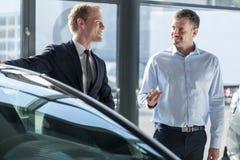 Car dealer showing vehicle. Photo of car dealer showing vehicle to male elegant client Stock Image